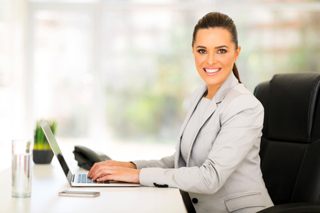 Photo for pretty female corporate worker working in office - Royalty Free Image