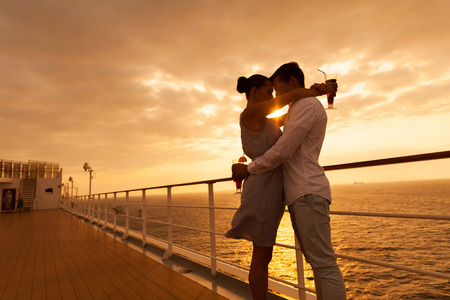 Photo pour romantic couple hugging with eyes closed at sunset on a cruise ship - image libre de droit