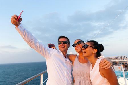 Photo pour group of friends taking self portrait using smart phone on cruise - image libre de droit