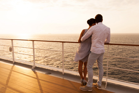 Foto de back view of young couple hugging at sunset on cruise ship - Imagen libre de derechos