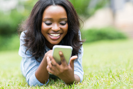 Foto de cheerful african american woman using smart phone - Imagen libre de derechos