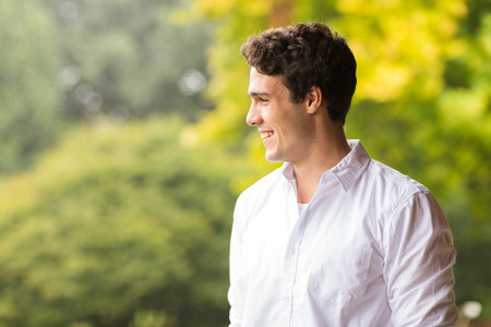 cheerful young man standing outdoors