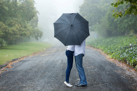 Foto de couple kissing behind the umbrella in the mist - Imagen libre de derechos