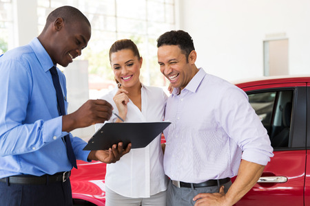 Photo pour african car dealer explaining sales contract to couple buying a car - image libre de droit