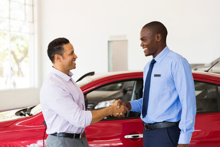Photo pour smiling african american car dealer handshake with customer - image libre de droit
