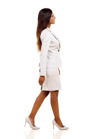 Photo for side view of young african american businesswoman walking on white background - Royalty Free Image