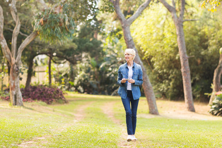 Foto per relaxed middle aged woman walking at the park - Immagine Royalty Free