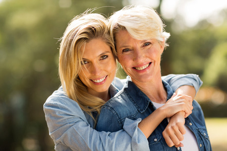 Photo pour close up portrait of mother and daughter hugging - image libre de droit