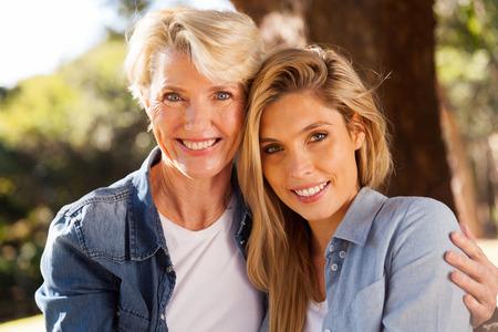 Photo pour portrait of cheerful senior mother and young adult daughter - image libre de droit