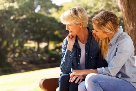 Foto de caring young daughter comforting senior mother - Imagen libre de derechos