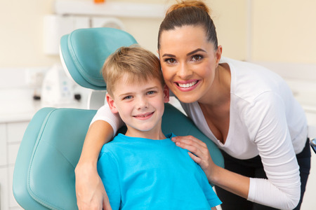 Photo pour beautiful mother hugging her son in dentist office - image libre de droit