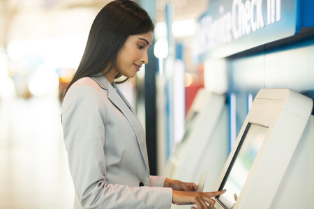 Foto de young business traveller using self service check in machine at airport - Imagen libre de derechos