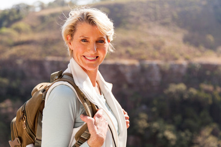 Photo pour happy mid age woman with backpack standing on top of the mountain - image libre de droit