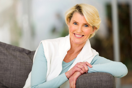 Foto per portrait of pretty middle aged woman sitting on sofa - Immagine Royalty Free
