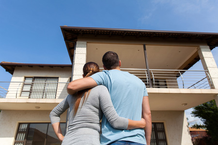 Photo pour rear view of young couple looking at their new house - image libre de droit