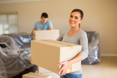 Photo for couple carrying boxes moving in new house - Royalty Free Image