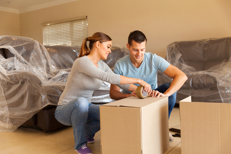 Foto de couple sealing moving boxes in their old home - Imagen libre de derechos