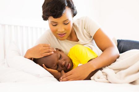 Foto de beautiful african mother embracing her sick son - Imagen libre de derechos