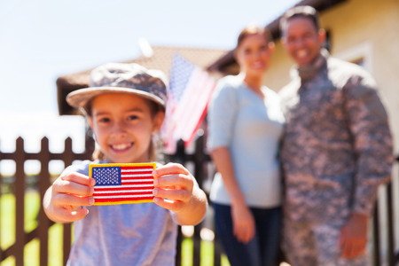 Foto de little girl holding american flag badge in front of parents - Imagen libre de derechos