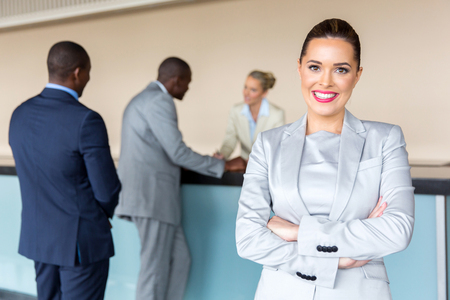 Photo for happy young businesswoman standing at hotel reception - Royalty Free Image