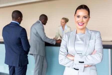 Photo pour happy young businesswoman standing at hotel reception - image libre de droit