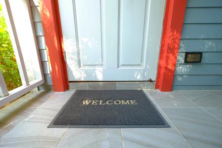Foto per Welcome doormat in front of the wooden door nearby a green garden - Immagine Royalty Free
