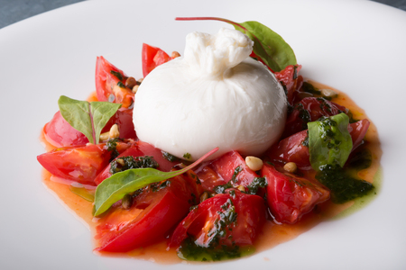 Photo for Burrata italian cheese snack with tomeatoes served on white plate - Royalty Free Image