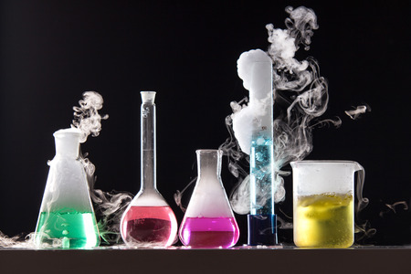 Foto de Glass in a chemical laboratory filled with colored liquid during the reaction - studio shoot - Imagen libre de derechos