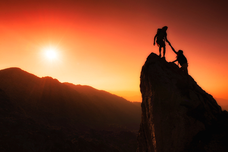 Foto de Team of climbers help to conquer the summit in teamwork in a fantastic mountain landscape at sunset - Imagen libre de derechos