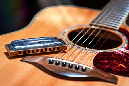 Foto de Acoustic guitar with country blues harmonica ready on stage - Imagen libre de derechos