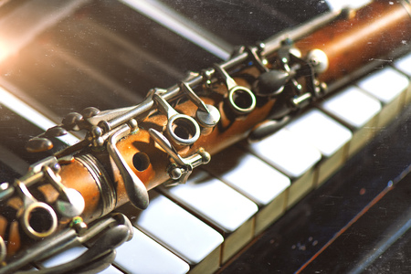 Photo for Vintage effect photograph. Antique clarinet leaning on piano keyboard. - Royalty Free Image