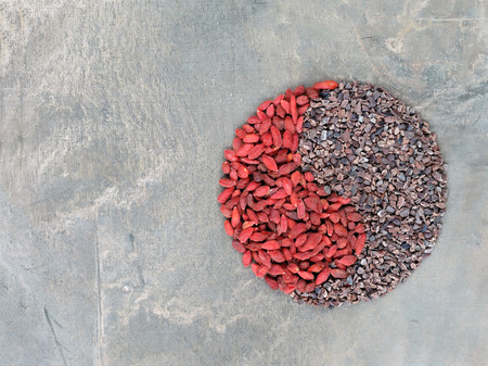 Photo pour Goji berries and cacao nibs shaped in Yin Yang symbol - image libre de droit