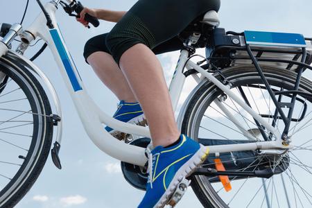 Photo pour Riding e-bike or electric bicycle, shot against blue sky, clean air concept - image libre de droit