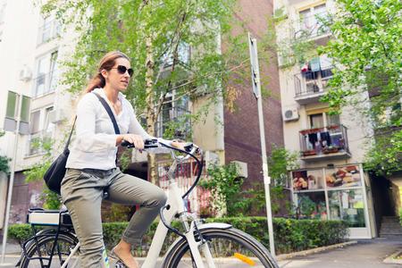 Photo pour E-bike commuter, riding through a city block - image libre de droit