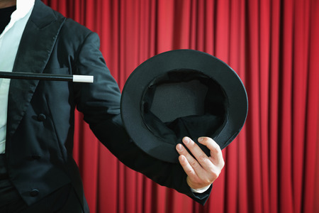 Magician showing empty top hat during performance on stage