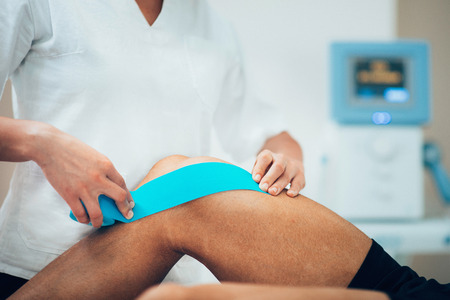 Photo for Physical therapist placing kinesio tape on patient's knee - Royalty Free Image