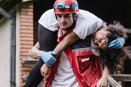 Foto de Rescue worker carrying disater victim - Imagen libre de derechos