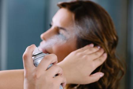 Foto de Spraying hair with hair spray in hair salon - Imagen libre de derechos