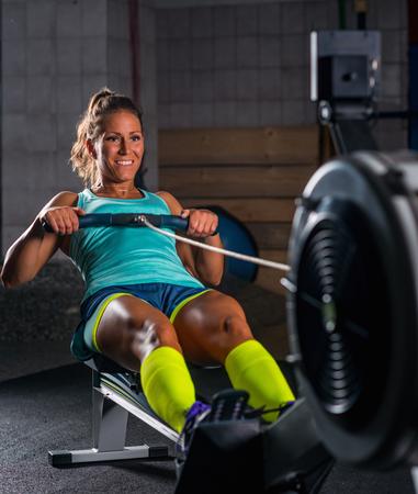 Photo for Woman athlete exercising on rowing machine - Royalty Free Image