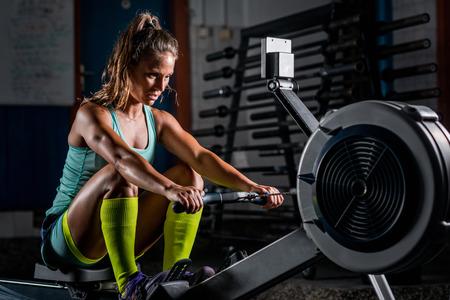 Foto de Woman athlete exercising on rowing machine - Imagen libre de derechos