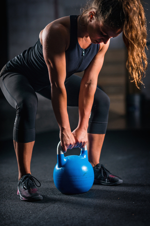 Photo for Woman athlete exercising with kettlebell indoors - Royalty Free Image