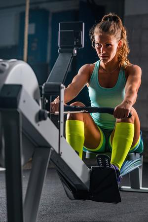 Photo pour Woman athlete exercising on rowing machine - image libre de droit