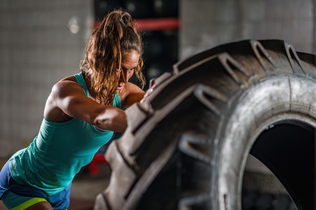 Photo for Woman athlete exercising with tire - Royalty Free Image