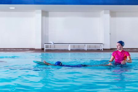 Foto de Boy having a swimming lesson with instructor - Imagen libre de derechos