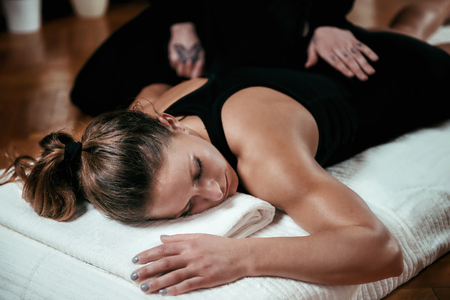 Foto de Beautiful young sporty woman enjoying shiatsu back massage, lying on the wooden floor, wearing black top - Imagen libre de derechos