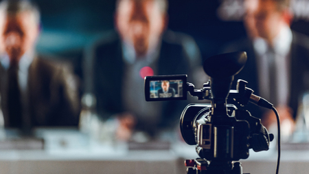 Photo for Professional digital camera at press conference, blurred speakers wearing suit background, live streaming concept - Royalty Free Image