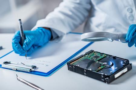 Foto de Forensic science expert examining hard drive - Imagen libre de derechos