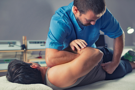 Photo for Physiotherapist doing healing treatment on man's back. Therapist wearing blue uniform. Osteopathy. Chiropractic adjustment, patient lying on massage table - Royalty Free Image