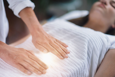 Foto de Female therapist performing Reiki therapy treatment holding hands over woman's stomach. Alternative therapy concept of stress reduction and relaxation. - Imagen libre de derechos