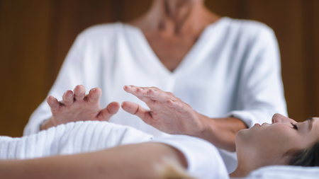 Foto de Professional Reiki healer doing Reiki treatment to young woman in health spa center. Healing and balancing heart and crown chakras. - Imagen libre de derechos